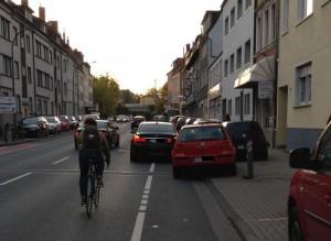 Gleich drei Autofahrer nehmen sich das Recht und parken auf Gehweg und Radfahrstreifen. Beim Ausweichen droht dem Radfahrer Gefahr von hinten und von den Autotüren der Falschparker.