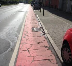 Vier Fahrspuren plus eine Parkspur für Autos. Dagegen nur ein schmaler Radfahrstreifen in jämmerlichem Zustand...